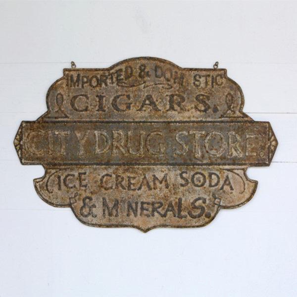 vintage embossed metal drug store sign